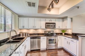 Extra Large Gourmet Kitchen:Granite counter and extended breakfast bar, refinished modern white cabinets, equipped w/ stainless steel appliances ( REFRIGERATOR INCLUDED), designer faucet, hardware , undermount lighting, and new wide-plank handscraped hickory laminate