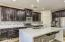 Gorgeous kitchen features waterfall quartz island, cherry espresso cabinets, stainless steel appliances, walk-in pantry.