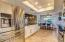 Stainless stell, bright white cabinets, and natural stone flooring