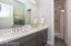 Double sinks, quartz counters, bath with floor to ceiling tile surround..
