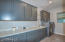 Quartz countertops, uppers and base cabinets, utility sink, & hanging rod.