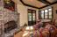 """Breakfast area with fireplace off the kitchen. Despite the grand design of the home, there are """"conversation areas"""" that feel cozy."""