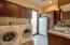 large laundryroom with built in pedestals for washer and dryer, stand up freezer and large prep station with sink and exit door to side yard