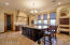large chefs kitchen with ovedrsized center island and chalkboard pantry door