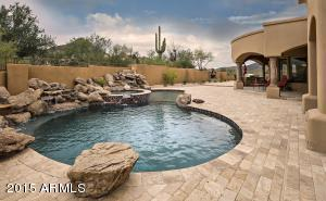 Diving pool with 4 waterfalls descending into pool and fire pit poolside.