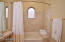 Luxurious travertine tiled Kohler tub/shower with bench style seat & curved curtain rod