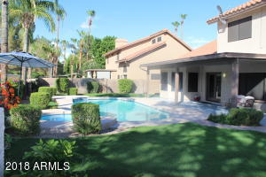 sparkling crystal clear pool in beautifully and professional landscaped back yard.
