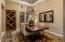 Formal dining room has contrasting coffered ceiling treatment and wine bottle storage.