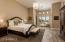 Large master bedroom, lofty ceilings and sitting area with designer window coverings.