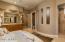 Master bath has a large travertine-tiled snail shower.