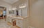 Downstairs in suite bath vanity has double sinks, sit down cosmetic area, ample light, stone counters and floors