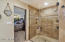 This large shower is stunning w/ 2 shower heads, beach entry and surrounded by stone.