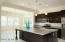 Oversized kitchen island and stainless steel appliances.