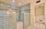 Spa like master bath with glass time and pebble flooring