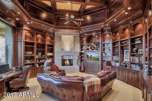 Stunning library with floor to ceiling wood decor and fireplace