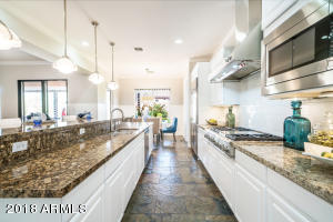 Let all the cooks in this kitchen- over 20' of granite island prep space!