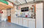 The garage is the perfect man cave with tons of built in cabinets.