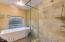 Sleek soaker tub, custom tiled shower
