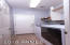 Laundry room featuring tile floors, ample storage, and easy access to/from garage.