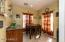 Separate dining area off kitchen flooded with beautiful natural light, recessed can lighting, tile flooring continued from the kitchen, and additional cabinets and matching counter!