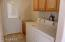 Comfortable inside laundry with its own sink and upper cabinets.