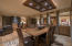 Custom made lighting fixture hangs over dining area. Dining open to great room and sitting area