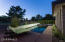 Twilight photo of pool & spa. Exterior patio is exposed aggregate