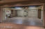 Custom built-ins, two storage areas, and epoxy floor detail this garage