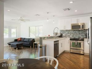 Bright white kitchen with quartz counter tops and stainless steel appliances.