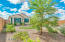 Professionally landscaped backyard features artificial turf, river rocks, gravel, plants and trees.