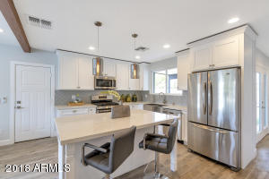 Kitchen has been beautifully updated with white cabinetry, generous sized island with bar seating, stainless appliances, and has direct access to the carport.