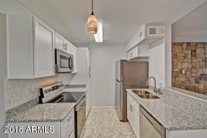 Eat-in kitchen with pendant lighting. Stainless steel appliances.