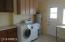 Large inside laundry room with extra storage and counter-top space is located just off the kitchen.