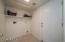 Laundry room with storage shelf above