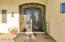 Iron and glass entry door greets each guest with elegance.