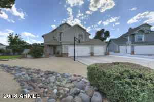 ) Front elevation of home with grass area, 3 car garage, parking for 6 on driveway in a private cul-de-sac.