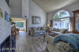 Light and airy Living Room with wood burning fireplace, vaulted tongue & groove ceiling, beautiful wood like tile flooring