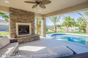 Stone faced gas fireplace is a perfect touch in this poolside gazebo. Enjoy the view looking toward the backyard where you'll find a putting green and firepit along with orange trees, palm trees and an easy care irrigated artificial turf.