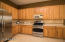 """kitchen with corian countertops, tile backspash, 42"""" hickory cabinets, upgraded stainless steel appliances, and GE profile gas range"""