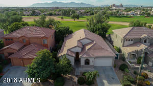 aerial of front of house, golf course, and mountains behind