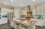 Large kitchen island, farmhouse sink, and industrial stove/oven with stainless steel hood makes the kitchen a showplace.