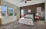 Large master bedroom has accent paint, pull-down shades, and remote controlled ceiling fan with light.