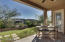 Bright, covered rear patio faces east toward a landscaped walking trail.