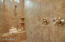 Huge master bath shower has beautiful tile, dual controls for rain shower head and flexible shower head, plus built-in seat.