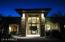 Imposing grand entrance at night with a wall of glass.