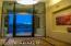 Floor to ceiling wall of glass and a niche for artwork make for a Grand Entry!