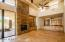 Soaring ceilings, rock fireplace, lighted cabinets and travertine floor in the Family Room portion of the home.