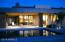 Poolside in the evening. The home is rimmed by antiqued copper metal trim, with Earth-toned rock-faced pillars.