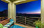 Balcony off guest room with view of sunset and city lights