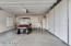 Extra wide garage has plenty of space for parking, along with extensive storage cabinets. (Golf cart sold separately)